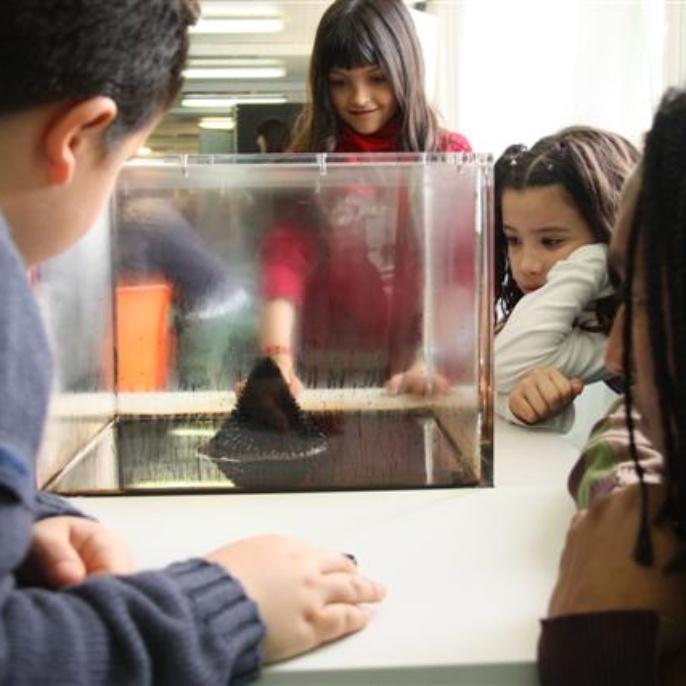 Kinder entdecken die wundersamen Eigenschaften von Ferrofluid.