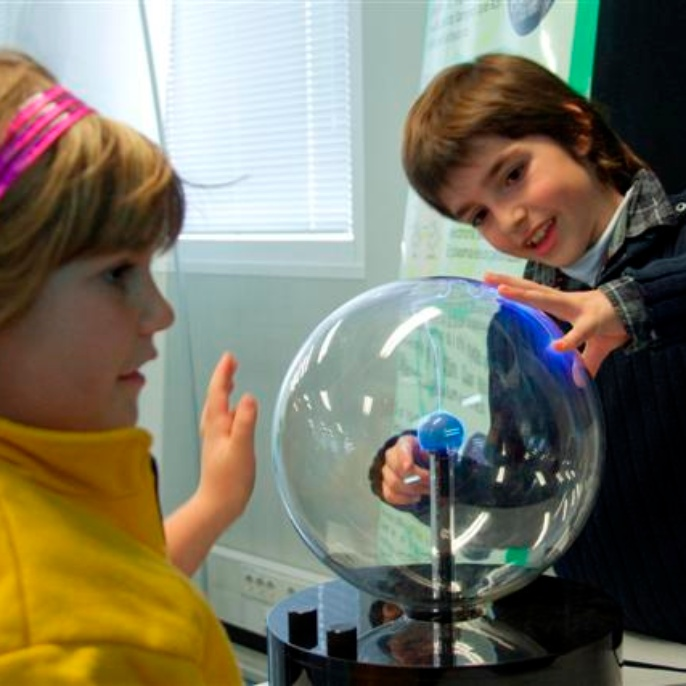Das Kind berührt die Plasmakugel und zieht mit dem Finger die Blitze magisch an.